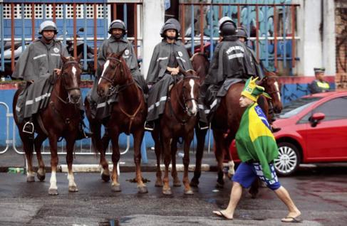 Un aficionado brasileño camina delante de un grupo de policía...