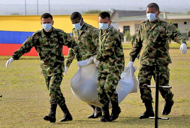 Soldados colombianos trasladan a un miembro de las FARC en Tame...
