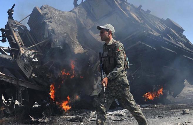 Un militar afgano pasa por delante de un vehículo quemado de la OTAN.