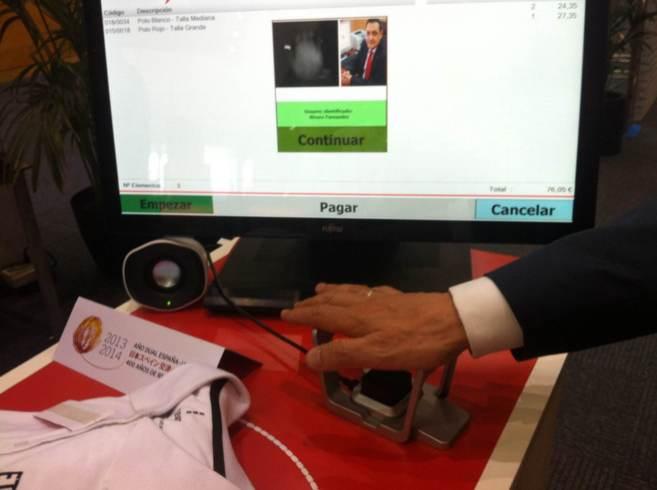 Un usuario utiliza el sistema PalmSecure en una tienda de roja.