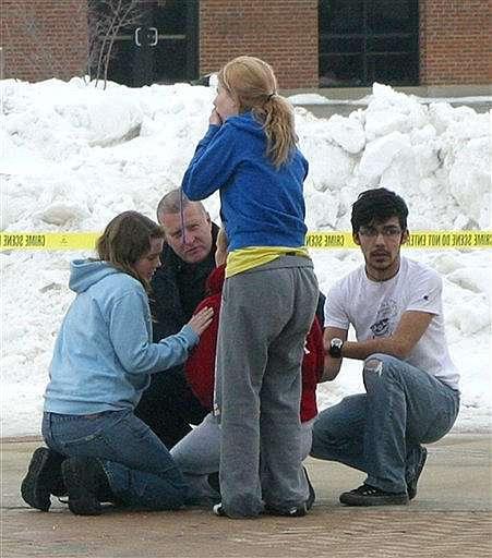 Unos jóvenes lloran después de un tiroteo.