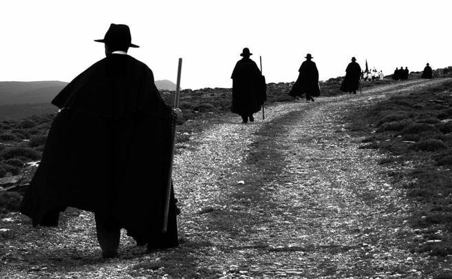 Los peregrinos de Portell desfilan con sombrero y capa negra, camisa...