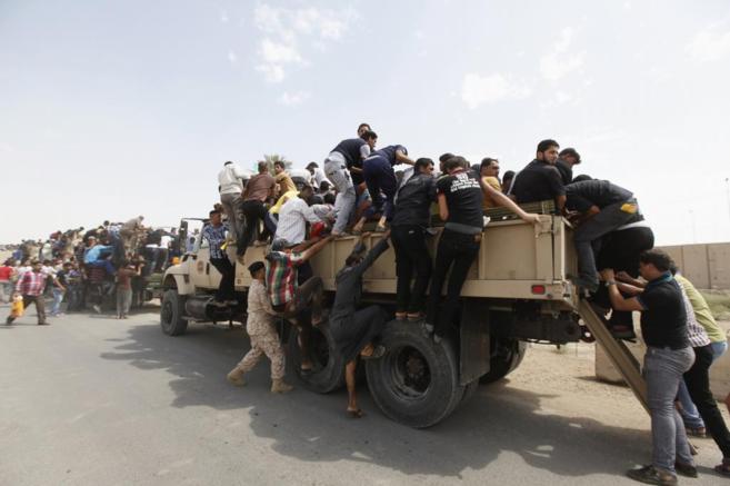 Voluntarios que se han unido al ejército iraquí se suben a camiones...