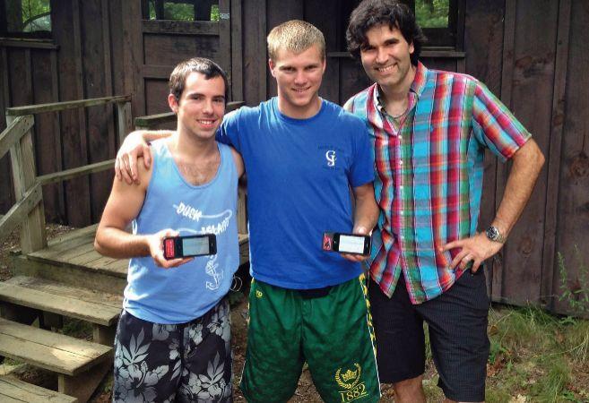 Tres jóvenes posan mostrando un dispositivo en la mano