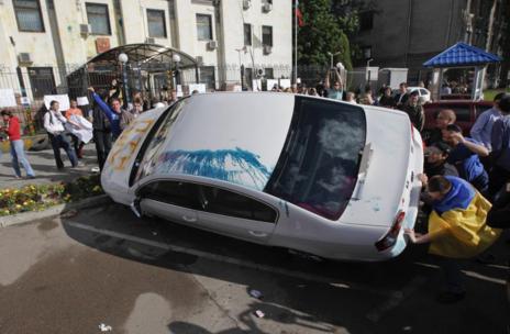 Manifestantes volcando un coche en la embajada rusa en Kiev