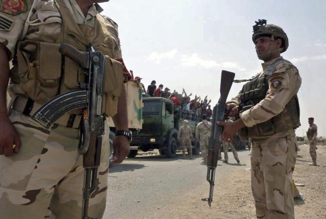 Soldados iraquíes transportan voluntarios a la base de Muthanna en...