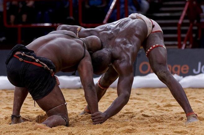 Una pareja de luchadores se enfrentan cuerpo a cuerpo en un...