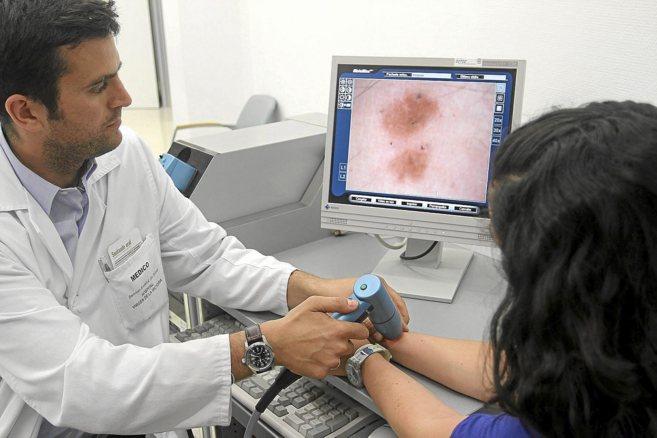 Un médico realizando un análisis de piel con un dermatoscopio a una...