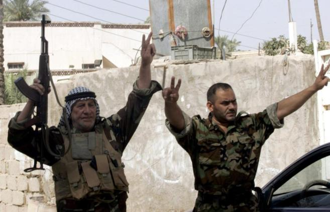 Soldados iraquíes hacen el signo de la victoria durante una patrulla...