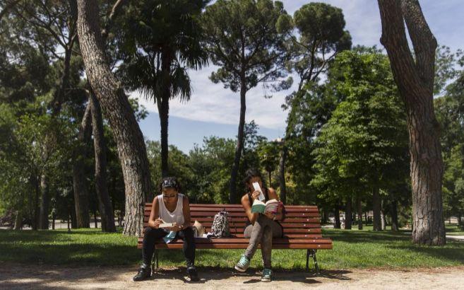 Dos chicas leen en un banco de un parque al aire libre