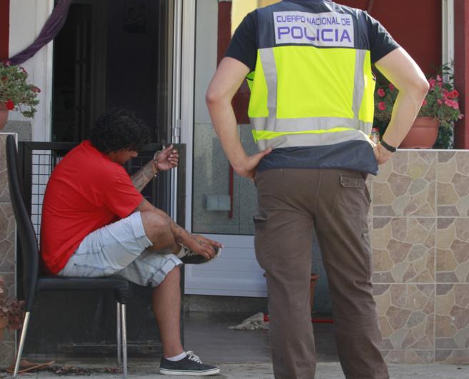 Uno de los detenidos custodiado por un agente de la Policía Nacional...