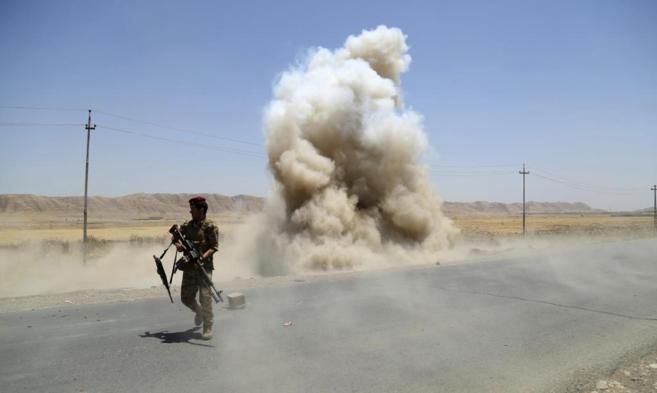 Un soldado kurdo se aleja de una explosión enTuz Khurmato, al norte...