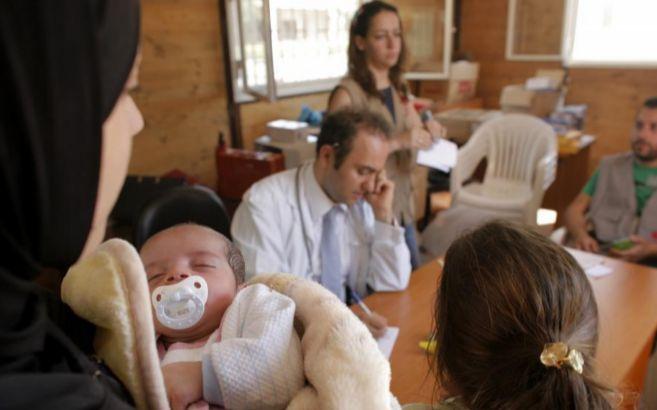 Una refugiada siria acude con su bebé a una clínica móvil de...
