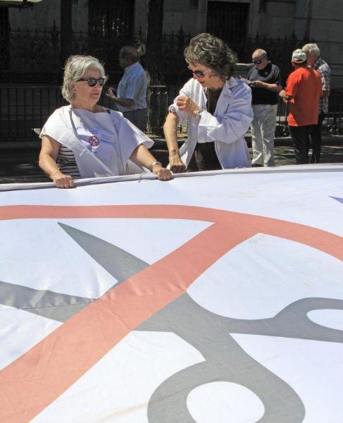 Dos mujeres con bata blanca delante de una pancarta contra los...