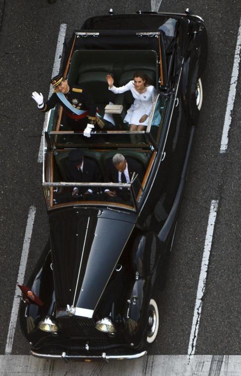 Los Reyes saludan durante el trayecto tras la proclamación