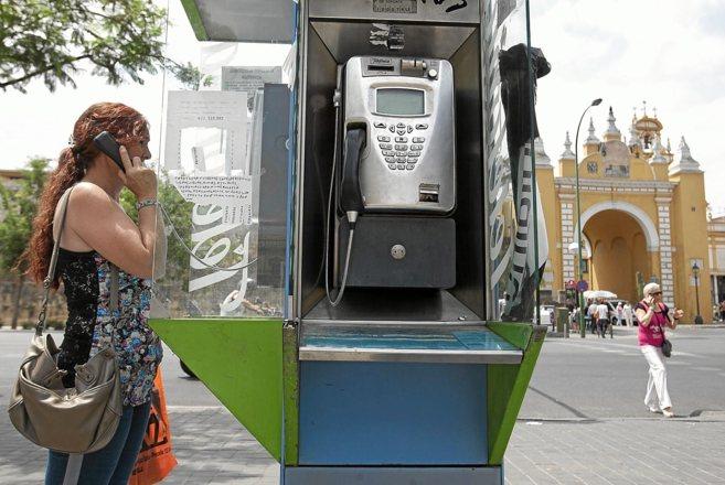 Una mujer hace una llamada desde una cabina en la Macarena. Otra, a la...