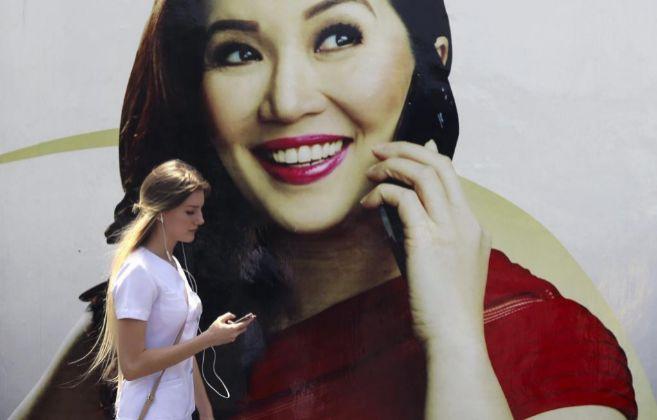 Una mujer mira su móvil mientras pasa por delante de un cartel...