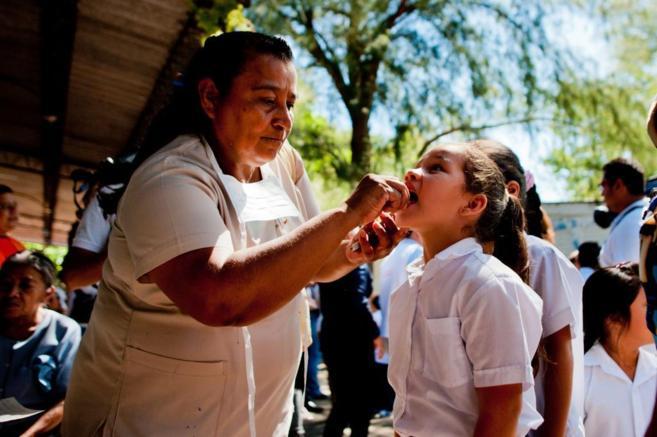 Una enfermera examina la boca de una niña.