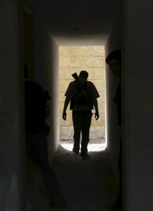 Un rebelde sirio regresa a un efidicio en el frente de Mleha. / B....