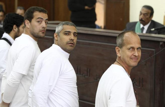 Peter Greste (dcha), Mohamed Fahmy (c) y Baher Mahmoud en el banquillo...