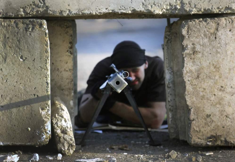 16 de Mayo de 2014. Un rebelde pro-ruso apunta con su rifle entre...
