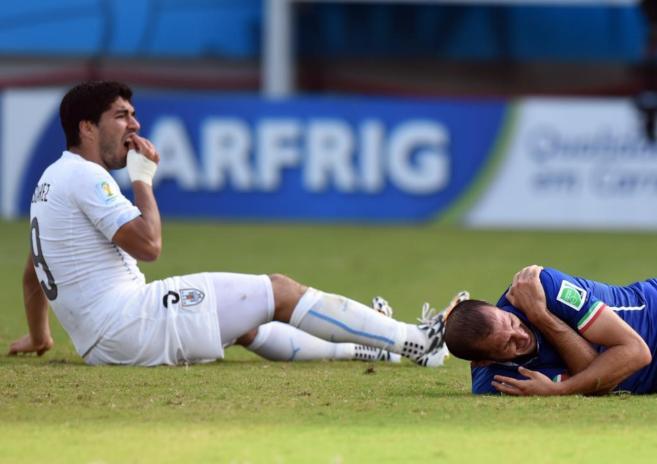 Chiellini, a la derecha, se duele en el suelo tras recibir el mordisco...