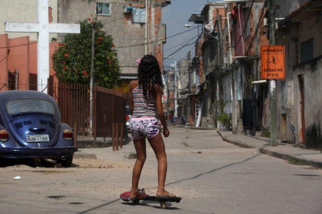 Una niña monta en patinete en un barrio de chabolas de Brasil.