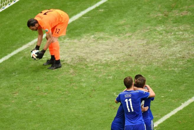 Dzeko celebra un gol mientras Haghighi recoge el balón de sus redes.