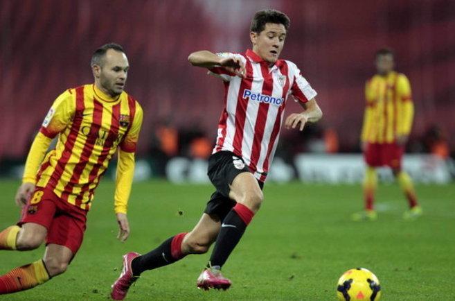 Ander Herrera conduce un balón ante la mirada de Andrés Iniesta.