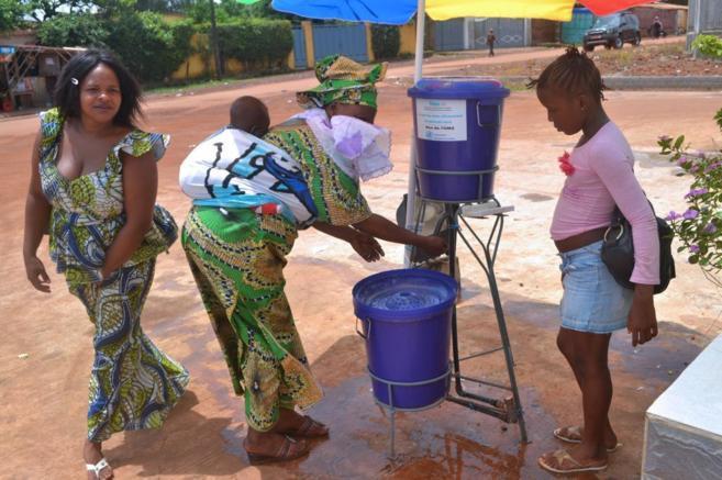 Mujeres lavándose las manos a la entrada del Hospital de Kipe (Guinea...