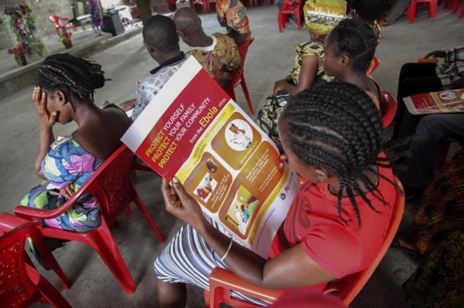 Una mujer lee un cartel con información sobre el virus del ébola...