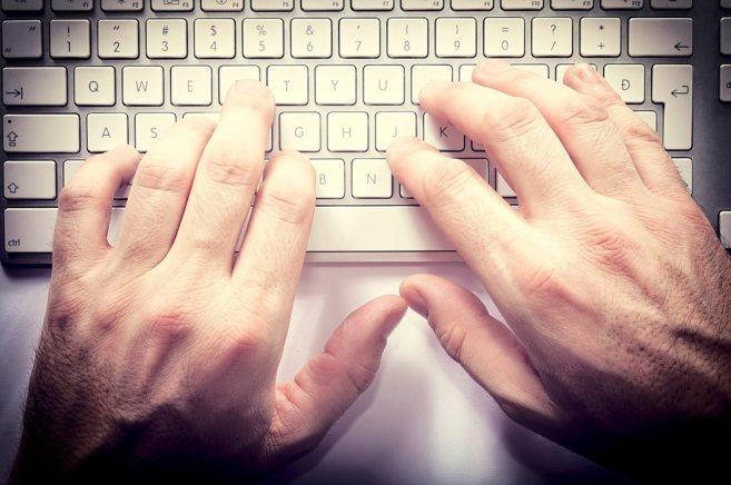 Manos en el teclado de un ordenador.