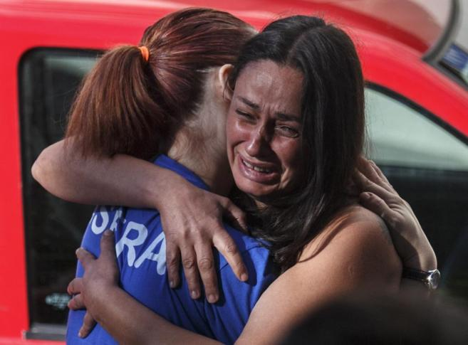 Dos mujeres se abrazan tras los incidentes ocurridos en el desahucio.
