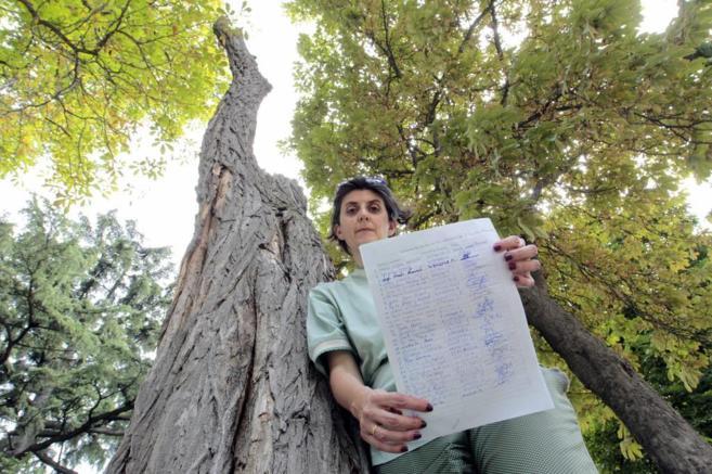 María Suárez posa con una hoja de firmas junto a un árbol seco y...