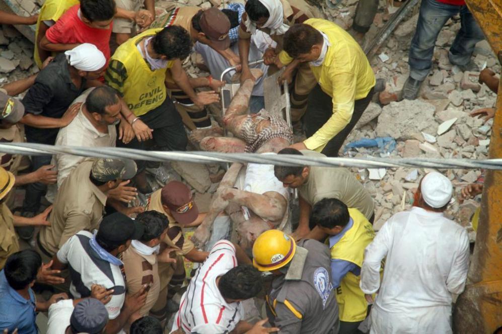 Los equipos de rescate sacan a una de las víctimas del derrumbe en...
