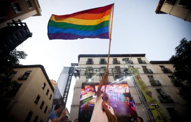 Un hombre agita una bandera arcoiris del Orgullo Gay en la plaza de...