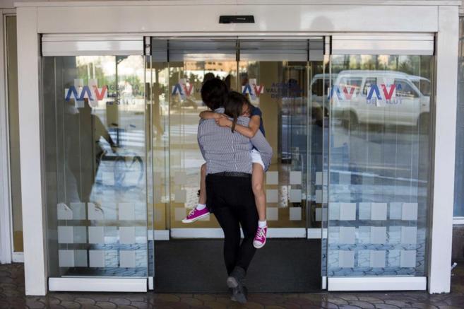 Una madre entrando en un hospital con su hija en brazos.