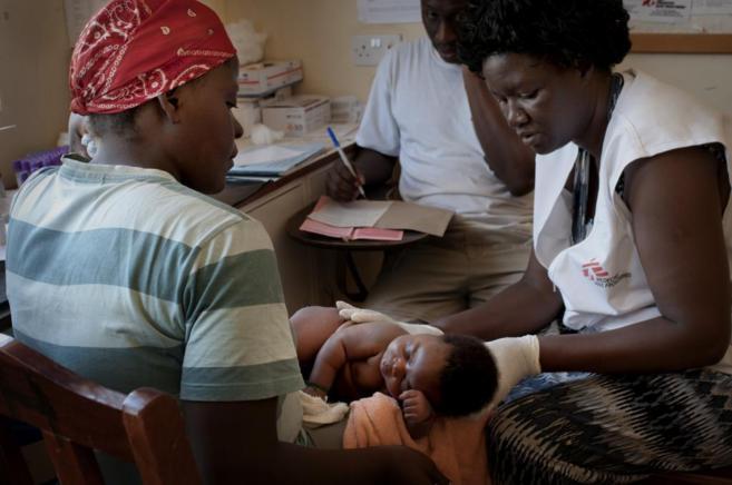 Un niño africano en brazos de su madre es examinado por personal de...