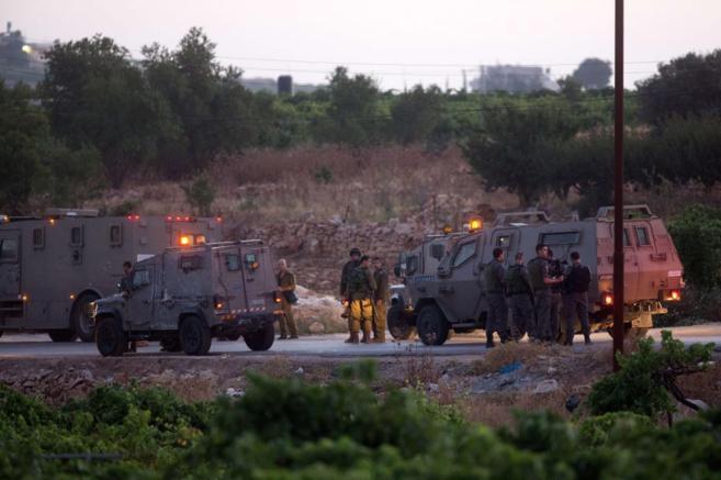 Soldados israelíes permanecen desplegados en la zona donde han...