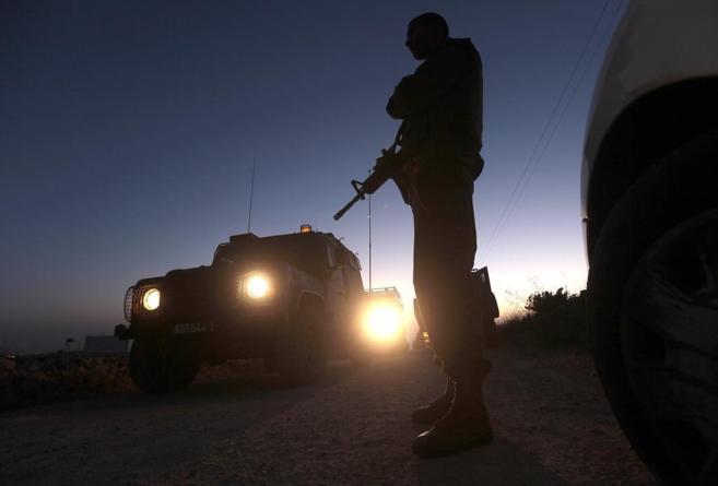 Un soldado israelí hace guardia cerca a donde fueron encontrados los...