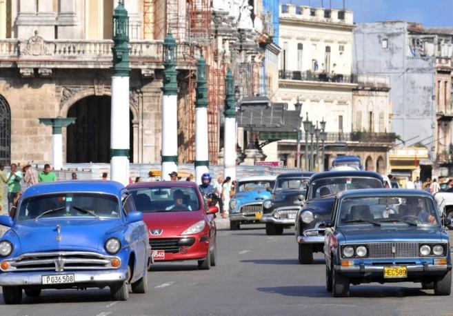 Varios coches circulan por una calle de La Habana.
