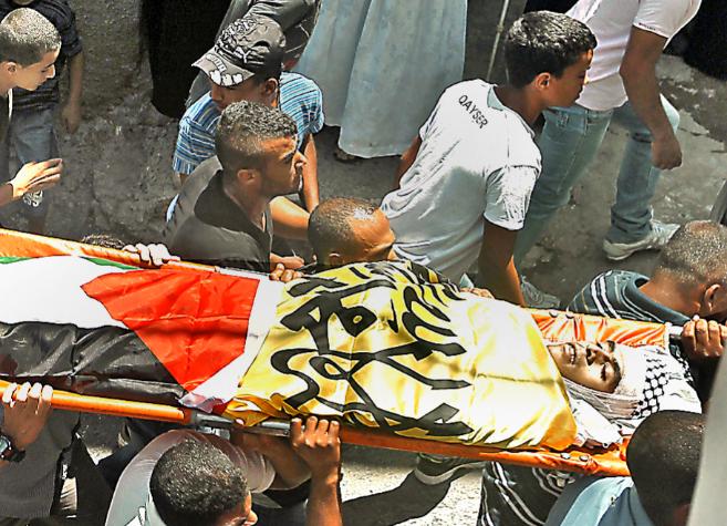 Jóvenes llevan en hombros el cuerpo del joven asesinado, Yusuf Abu...