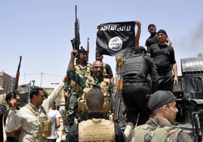 Fuerzas de seguridad iraquíes despliegan una bandera del ISIS durante...