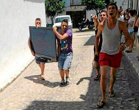 Varias personas portan un plasma tras desvalijar una de las casas.