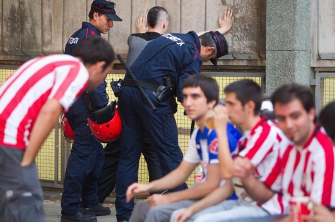 Dos agentes de la Ertzaintza cachean a un aficionado en la previa de...