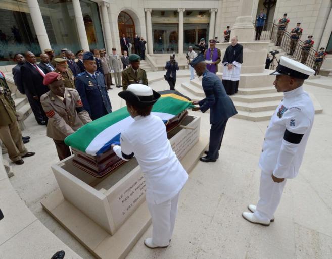 Oficiales del ejército sudafricano colocan una bandera en el ataúd...