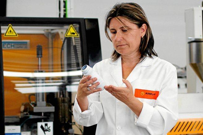 Una investigadora con un ejemplo de botella biodegradable.