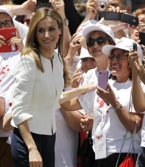 La Reina saluda a los asistentes al acto de la Cruz Roja.