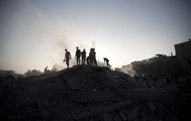 Palestinos inspeccionan los daños tras el ataque aéreo israelí en...