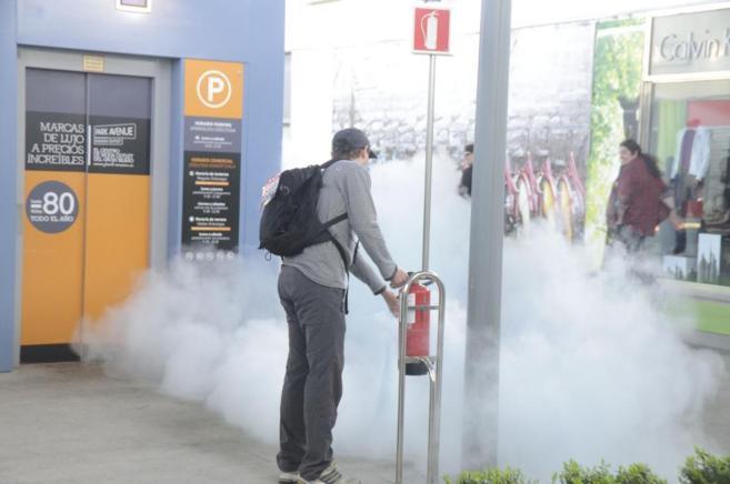 Un hombre apagando un fuego en un centro comercial del País Vasco.